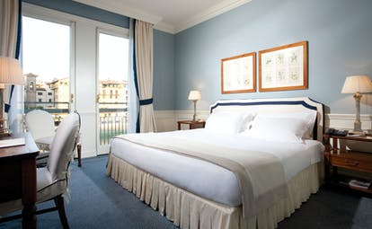 Bedroom with large double bed, blue colour scheme and balcony