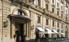 Beige stone exterior of grand hotel Savoy in Florence with awnings outside