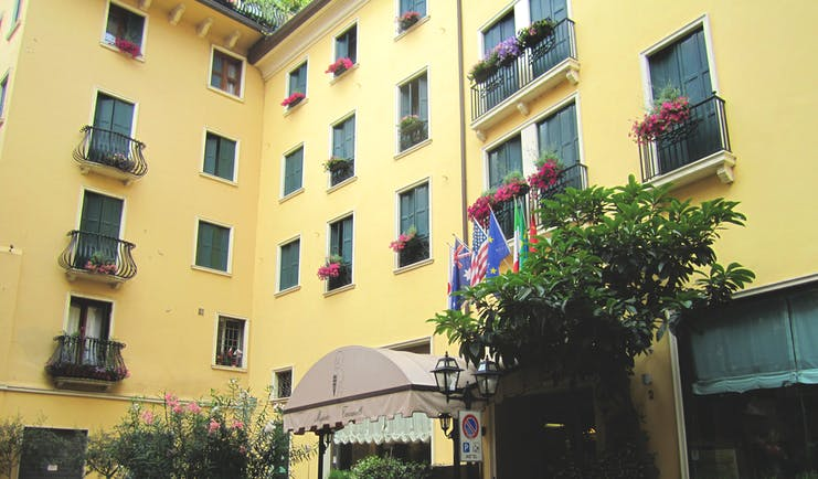 Majestic Toscanelli Padua hotel exterior yellow building juliet balconies window boxes with pink flowers
