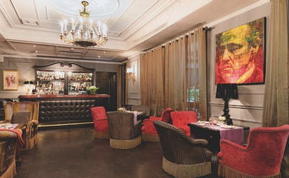 Bar and cafe at the Baglioni Hotel Carlton, with red and brown arm chairs placed around the wooden floors with a bar at the back of the room