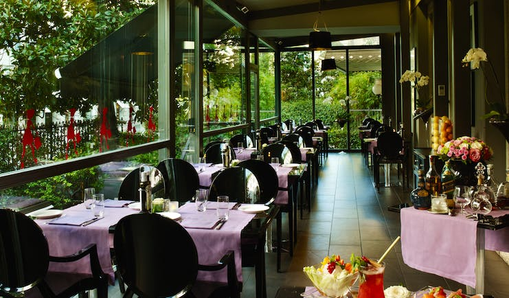 Dining area at the caffe e terrazza baglioni restaurant with black seats and black tables covered with pink table cloths