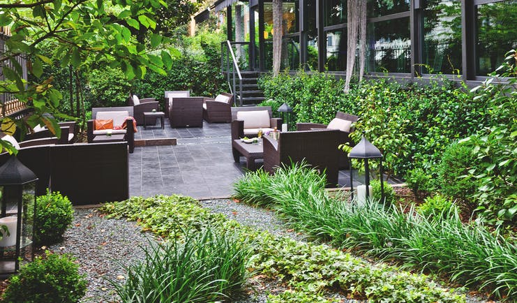 Terrace gardens at the Baglioni Hotel Carlton with trees and greenery and scattered cushioned chairs