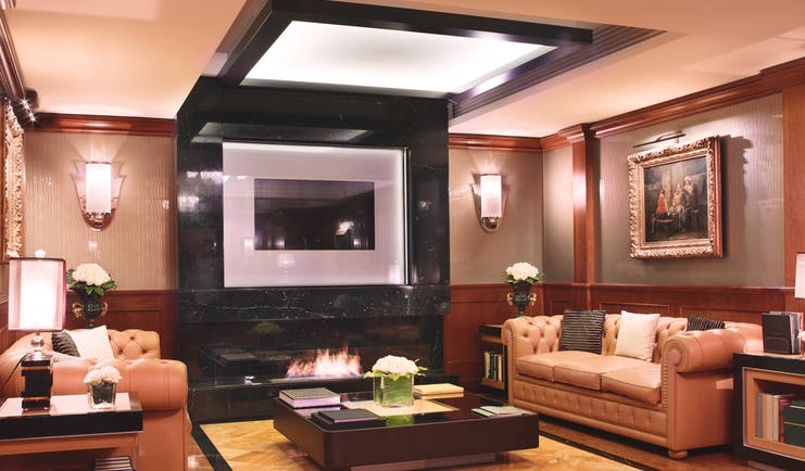 Baglioni Hotel Carlton lonny with leather sofas an electric fire and wooden wall pannels