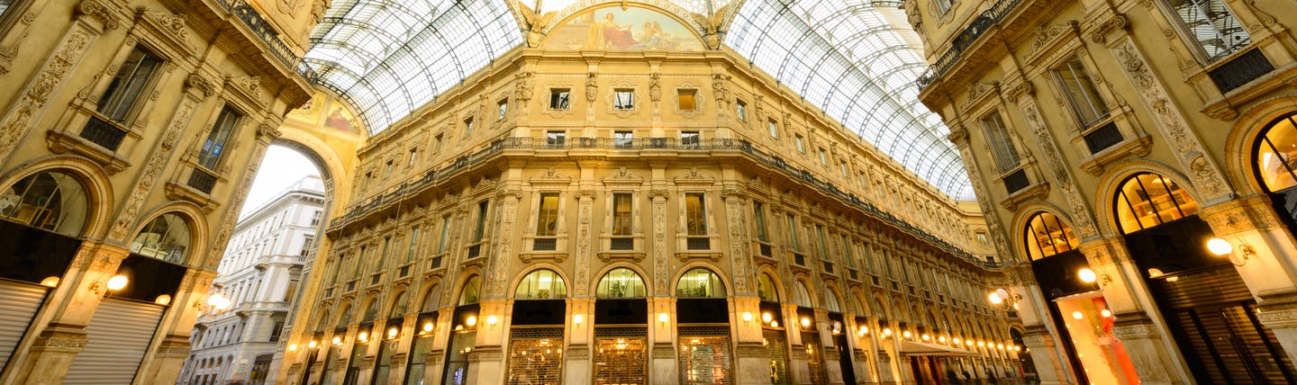 Ornate glass roof of the Galleria Vittorio Emanuele with elegant buildings in Milan