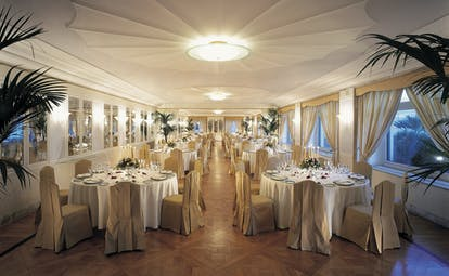 Dining room set up with large circular tables and elegant table cloths