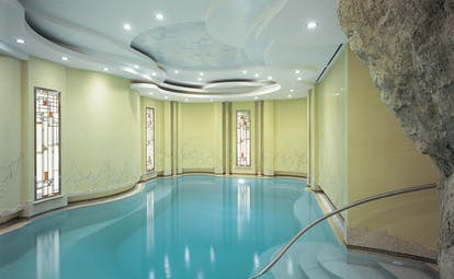 Indoor swimming pool with yellow walls and wall lights