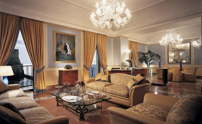 Lounge with large chandeliers, sofas and draping gold curtains