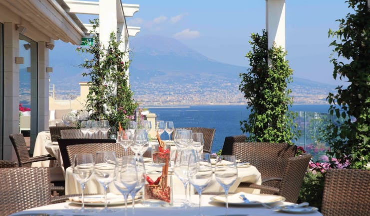 Outdoor restaurant dining area with views over mountains with tables set up on the terrace
