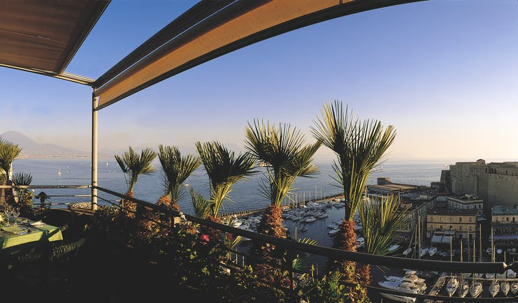 View of the roof garden at the Grand Hotel Vesuvio with palm trees on the roof and overlooking the city and the blue sea
