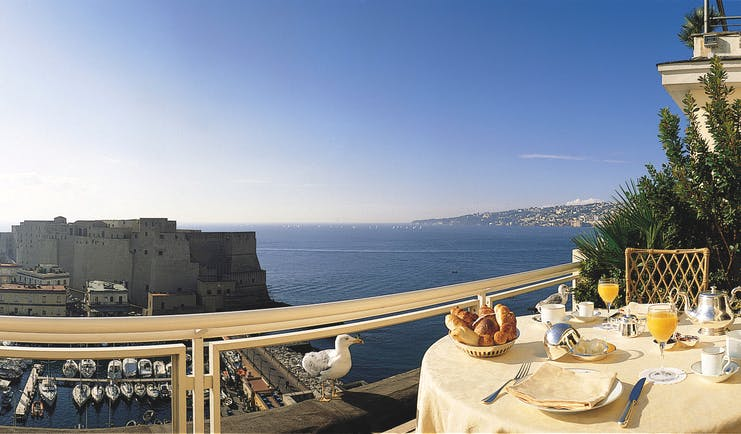 View from a balcony at the Grand Hotel Vesuvio looking over Naples and the blue sea