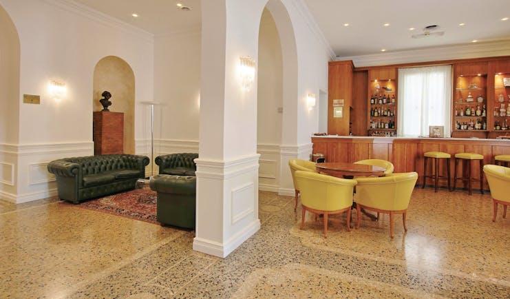 Rechigi Park Hotel bar, bright elegant decor, tiled floors, wooden bar, chairs, leather sofa, archway