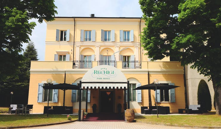 Rechigi Park Hotel exterior, hotel building and entrance, traditional Italian architecture, shuttered windows, canopied entrance, lawn, trees