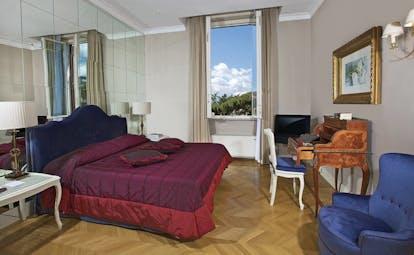 Aldrovandi Villa Borghese Rome executive suite bedroom bed desk mirrored wall open window