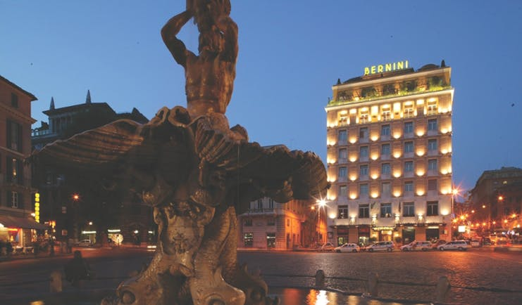 Bernini Bristol Rome hotel exterior at night hotel lit up fountain in foreground