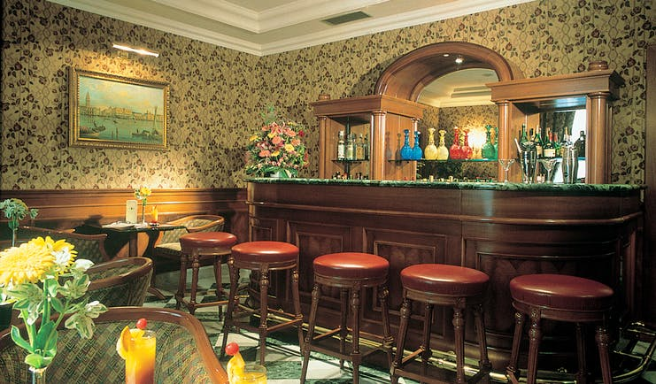 Bar with red bar stalls, wood pannelled bar and drinks