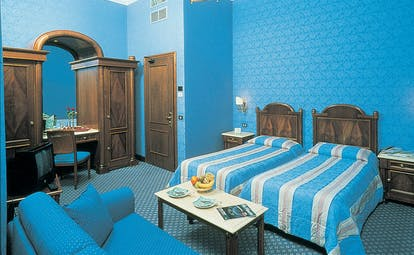 Twin bedroom with blue colour scheme, two single beds and a dressing table