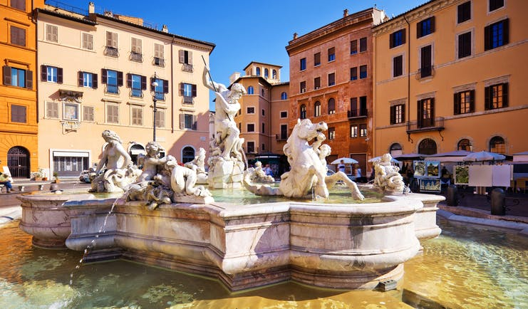 Baroque fountain of Neptune with water around and ochre houses at the Piazza Navona in Rome