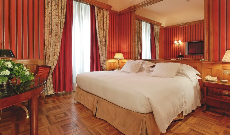 Deluxe room with wooden parquet floor and red wallpaper at the Grand Hotel Sitea Turin