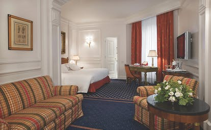 Grand Hotel Sitea Turin junior suite with striped sofa and orange curtains