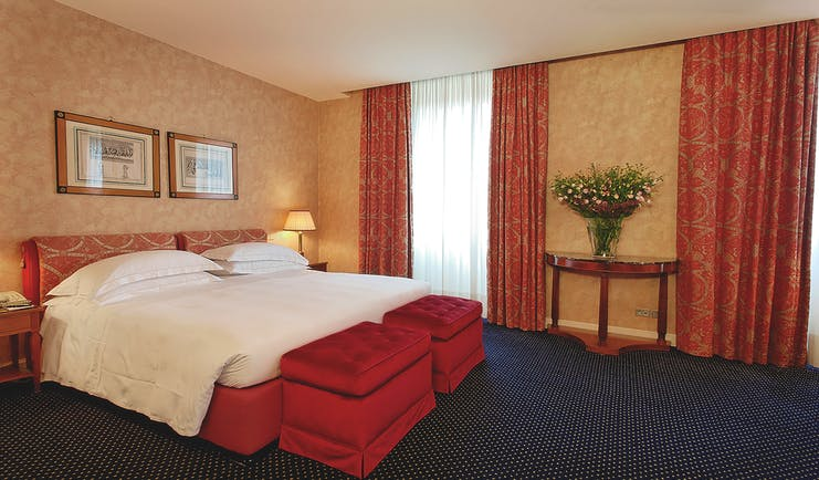 Double bedroom with red curtains and blue carpet at the Grand Hotel Sitea Turin