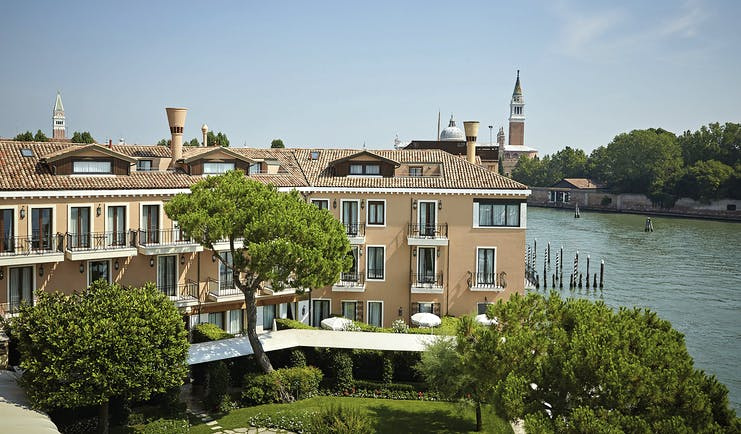View of the exterior of the Belmond Hotel Cipriani with greenery infront of the hotel and water behind