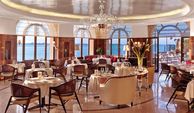 View of the restaurant in the Belmond Hotel Cipriani with a red and orange colour scheme with big arching windows round the circumference of the room with sea views