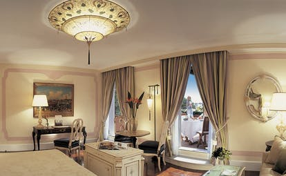 Belmond Hotel Cipriani cream and grey colour themed suite, with king sized bed, yellow lamp lighting and a chandelier