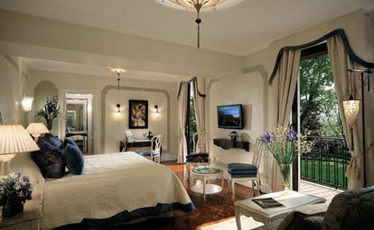 Belmond Hotel Cipriani Suite with king sized met, double doors leading out onto a balcony and a chandelier