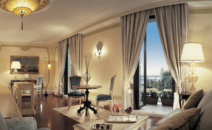 Belmond Hotel Cipriani cream and gray colour-themed suite with a king sized bed