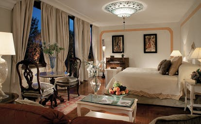 Belmond Hotel Cipriani suite with a king sized bed, cream and beige colour scheme, a chandelier and paintings on the walls