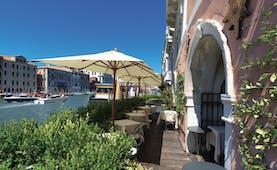 Ca Sagredo Venice terrace outdoor seating area overlooking canal dining tables umbrellas