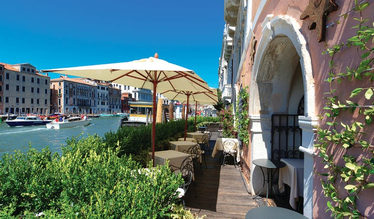 Ca Sagredo Venice terrace outdoor seating area overlooking canal dining tables umbrellas