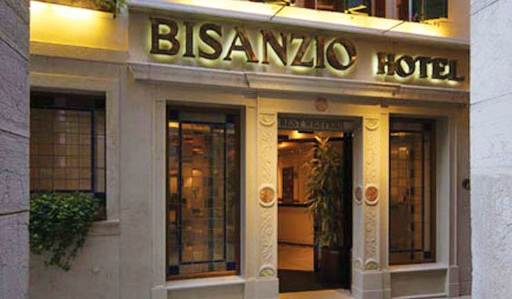 Entrance to the Bisanzio Hotel with the sign lit up in black above the wooden door