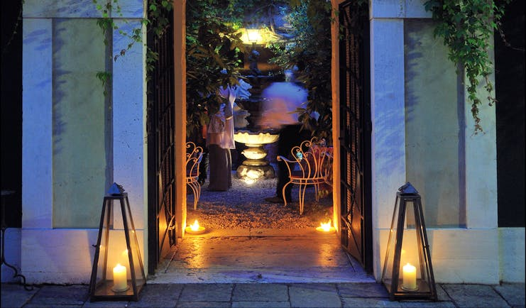 Entrance to Hotel Flora at dusk with vines creeping up the hotel walls and a large arch doorway