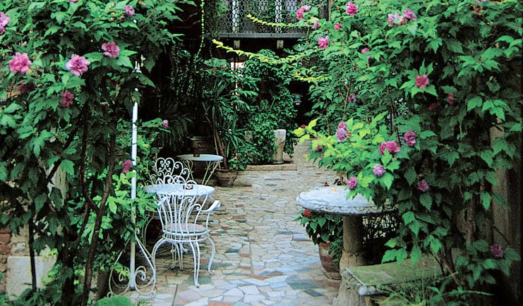 Hotel Flora Venice garden patio outdoor seating area shrubs