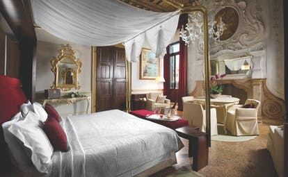Palazzo Giovanelli Venice Foscarini suite large bed and room dining area ornately decorated
