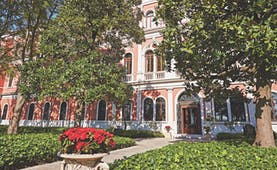 San Clemente Palace Venice hotel exterior pink building trees and shrubbery