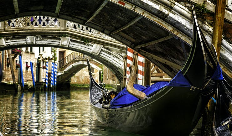 Gondola under low bridge in Venice with reflections on water