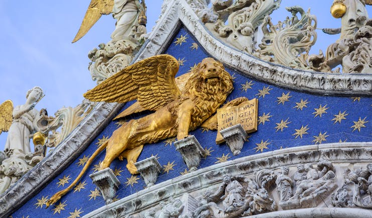 Golden lion on front of the blue and gold of St Mark's Basilica in Venice