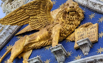 Golden lion statue on front of ornate blue and golden starred facade in Venice