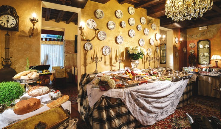 Breakfast buffet spread with large chandelier hanging from ceiling, wood pannelled ceilings and food laid out on top of table cloth