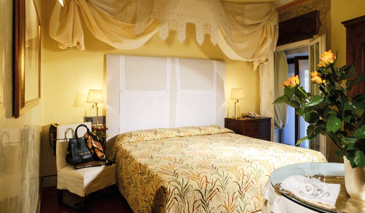 Superior suite with yellow and cream colour scheme, large double bed with drapes and flowers