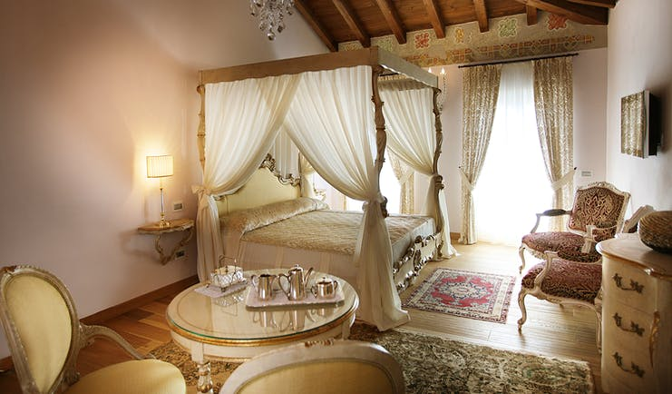 Bedroom with four poster bed with drapes, curtains and chandelier