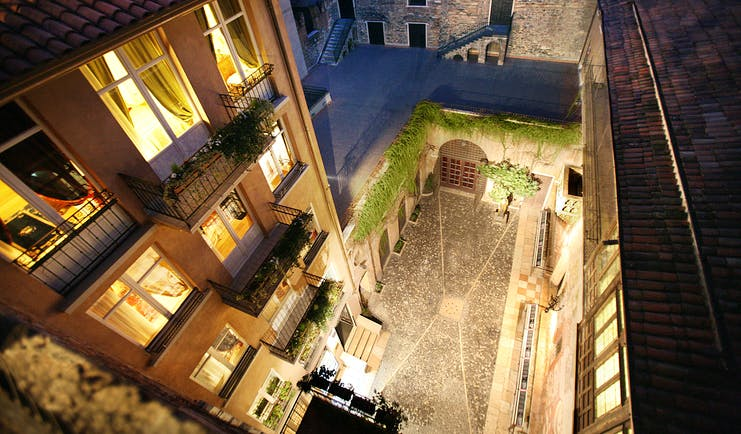 Courtyard outside between hotel buildings with vines growing up the buildings