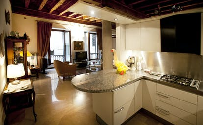 Kitchen suite with cooking equiptment, living area and doors opening onto balcony
