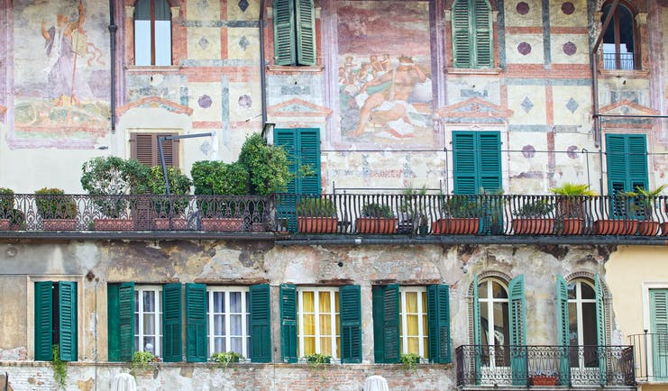 Ornate murals in pink and green on wall of old building with green shutters in Piazza delle Erbe Verona