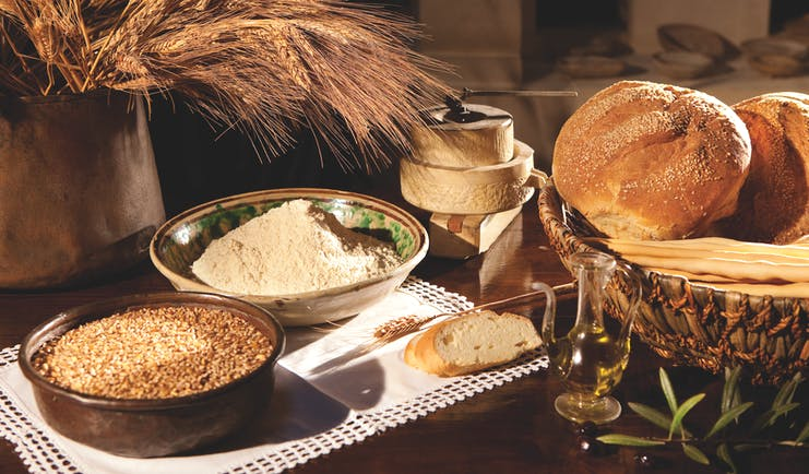 Rounds of bread and bowls of grain on table
