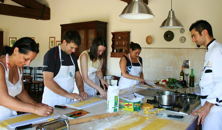 People in kitchen standing at table preparing food with chef watching