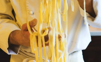 Chef in whites holding strands of freshly made tagliolini