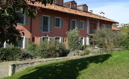 Pink low building with green shutters Villa d'Amelia Piemonte